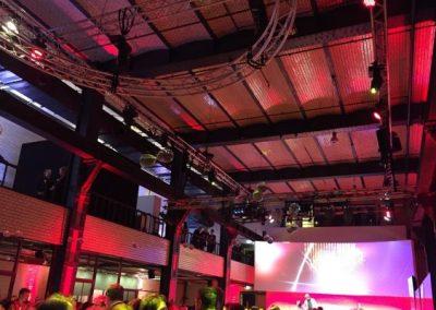 Blick auf Bühne, Publikum davor, Traversen mit Scheinwerfern, rotes Licht, große Leinwand über Bühne