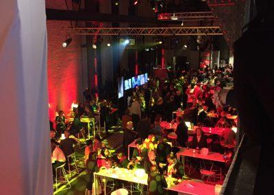 Rote Saalbeleuchtung, Gäste an langen Tischen, Traversen mit Scheinwerfern, Bild von oben in Saal