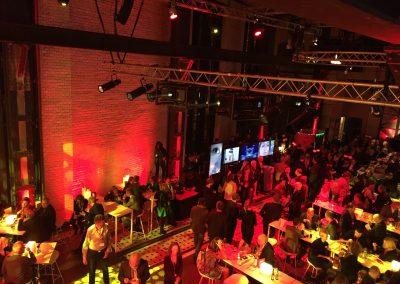 Rote Saalbeleuchtung, Gäste an langen Tischen, Traversen mit Scheinwerfern, Bild von oben