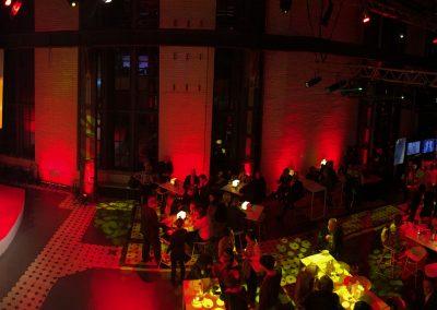 Sapophon Spieler und DJ auf Bühne, lange Tische davor, rote Beleuchtung im Saal
