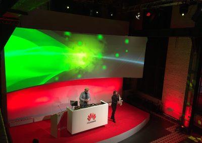 Bühne mit Saxophon Spieler, DJ, rotes Licht, Leinwand mit grünem Licht über Bühne