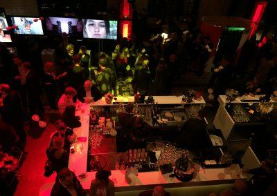 Blick von oben auf Bar, Leinwände mit Gesichtern und Bildern im Hintergrund, Menschen an Bar, Rote Beleuchtung