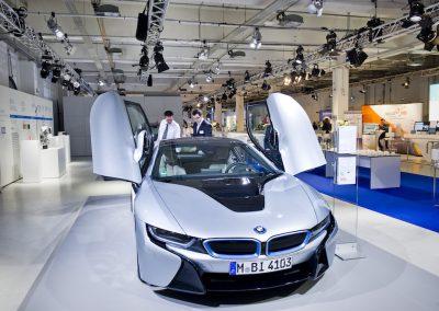 Silberner BMW wird präsentiert, 2 Männer schauen sich das Auto an