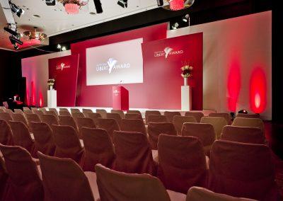 leere Stuhlreihen vor Bühne, rotes Licht, Mikrofone auf Bühne,