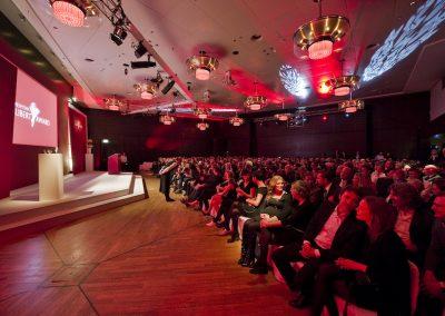 Publikum vor Bühne, rote Beleuchtung, Goldene Lampen und Lichtornamente an Decke, Bühne mit Rednerpult in Beige