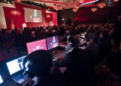 Blick aus Regie auf Bildschirme und Bühne auf der gerade ein Redner spricht
