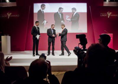 3 Männer auf Bühne übergeben einen Preis, Fotografen davor