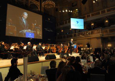 Mann spricht auf Bühne in Mikrofon, Orchester dahinter, 2 große Bildschirme über Bühne