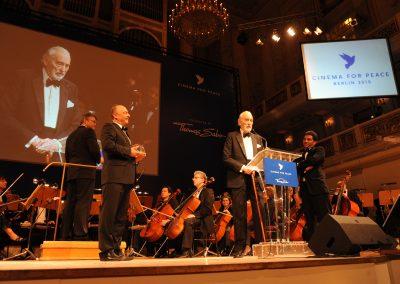 Mann in schwarzem Anzug mit Fliege spricht auf Bühne an Mikrofon, Orchester mit Instrumenten dahinter