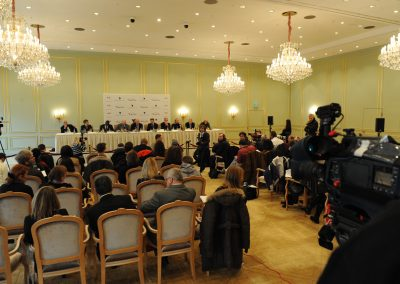 Pressekonferenz, weisse Kronleuchter und Sprecher auf der Bühne, Journalisten im Publikum