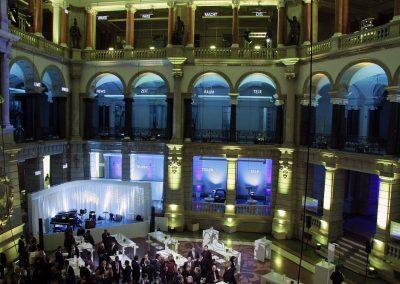 Veranstaltung, blau beleuchteter Hintergrund, Gäste vor Bühne an weissen Tischen