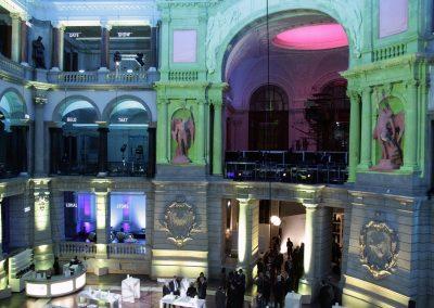 Veranstaltung, bunt beleuchteter Hintergrund, Gäste an weissen Tischen