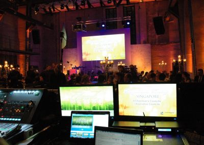 Mischpult und Bildschirme im Vordergrund, Gäste an Galatischen und Leinwand über Bühne im Hintergrund, Leuchter auf den Tischen