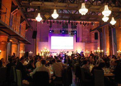 Gäste an Dinnertischen, große Kronleuchter an Decke, im Hintergrund Leinwand über Bühne